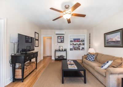 Rittenhouse Square apartment living room with restored hardwood floor and built-in bookshelves